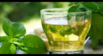 te-verde-servido-en-un-vaso-corto-junto-a-hojas-de-te